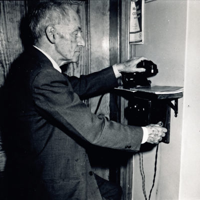 Castine Resident Willis Ricker using the crank phone, 1956. Photo by Ed Langolis.