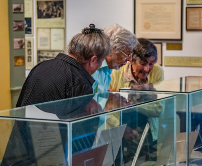 Dixie Gray, Paul Gray, and Virginia Bourne look in display cases at the 2017 Season Opening Reception
