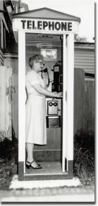 Kath Gray making the last call in the booth on Water Street, Castine, before the operator-assisted crank telephone system was upgraded to a dial system in 1956. Photograph by Ed Langlois, CHS Collections