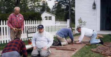 President Emeritus Jim Day and volunteers install bricks in front of the Abbott School.