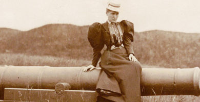 Woman sitting on cannon at Fort George, late 19th century. Castine Historical Society Collections.