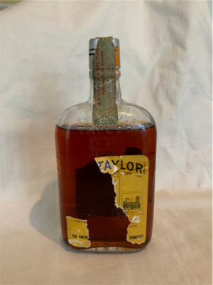 """A similar bottle of Old Taylor bourbon sold at Sotheby's recently for $800. Old Taylor Bourbon was named in honor of Edmund Haynes Taylor, one of Kentucky's original bourbon aristocrats and the """"father of the modern bourbon industry."""" In 1894, Taylor and his sons organized a corporation under the name of """"E. H. Taylor, Jr. & Sons"""". Donated by Rev Courtley."""